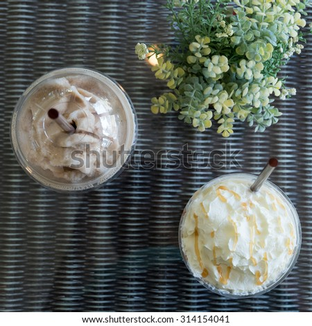 iced frappe coffee in plastic mug put on the rattan weave table in coffee shop cafe - stock photo