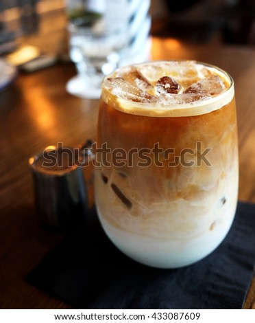 Iced latte served in the glass on wooden table at restaurant (Low-key Picture Style) - stock photo
