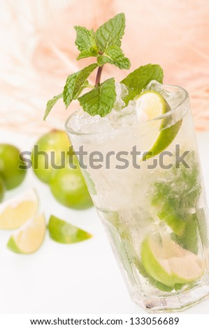 Iced Lime Mojito cocktail with limes and a straw hat background - stock photo