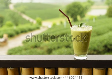 Iced matcha green tea latte, behind a tea plantation