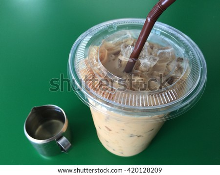 Iced milk coffee in plastic cup with brown straw and sugar syrup on green table. soft and selective focus.(side view) - stock photo