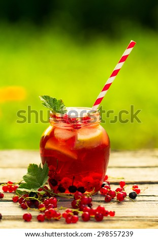 Iced Red currant drink on wooden table