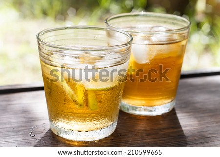 iced tea and lemon with nature background - stock photo