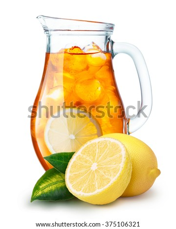 Iced tea in a pitcher. Jug full of iced tea or lemonade with lemons on foreground - stock photo