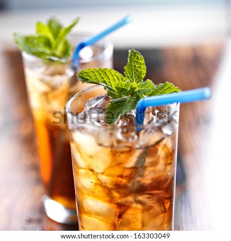 iced tea with blue straw and mint garnish - stock photo