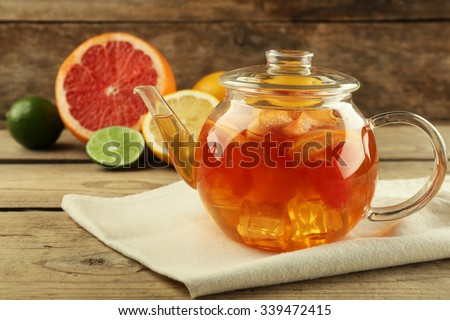 Iced tea with lemon and grapefruit on wooden background - stock photo