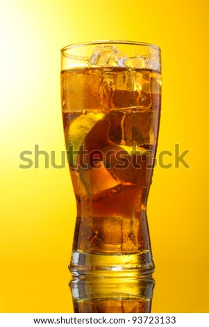 Iced tea with lemon and lime on yelow background