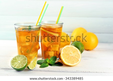 Iced tea with lemon on light wooden background - stock photo