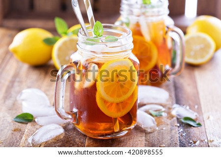 Iced tea with lemon slices and mint on rustic background - stock photo