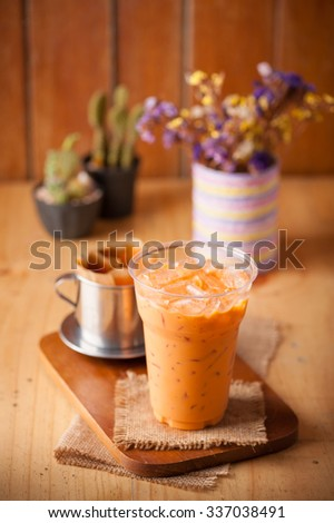 Iced Thai milk tea in plastic glass on wood table in cafe - stock photo