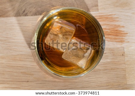 iced wiskey on wood floor from above - stock photo