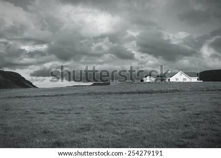 Iceland countryside landscape - generic farm house. Black and white toned image. - stock photo