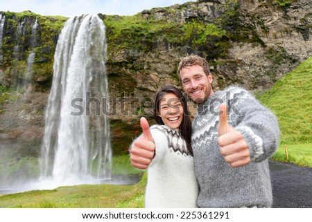 Iceland couple thumbs up wearing Icelandic sweater by Seljalandsfoss waterfall on Ring Road in beautiful nature landscape on Iceland. Woman and man model in typical Icelandic sweater. Multiracial. - stock photo