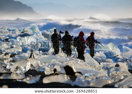 ICELAND - MARCH 26, 2015: Photographers views the sunrise amidst the blocks of ice from the glaciers that break up and washed ashore by the strong waves of the North Atlantic sea in Iceland.  - stock photo