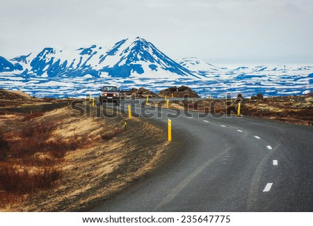 Iceland road landscape with clouds and amply field - stock photo