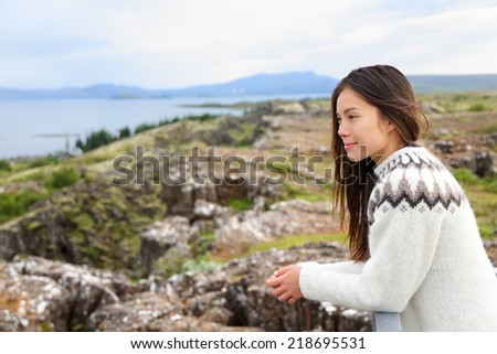 Iceland - woman in Icelandic sweater looking at Thingvellir place of Althing, the first parliament in the world. Girl at tourists destination sightseeing. - stock photo