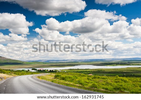 Icelandic countryside landscape in summer season. Bright summer day with nice puffy clouds. Laugarvatn lake, west Iceland. - stock photo