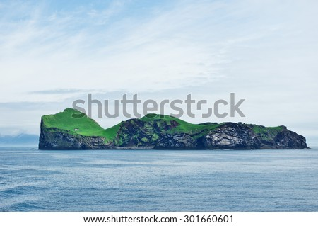 Icelandic island with small white house on it - stock photo