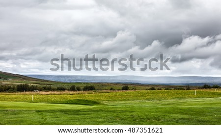 Icelandic landscape with view on green meadow with beautiful sky