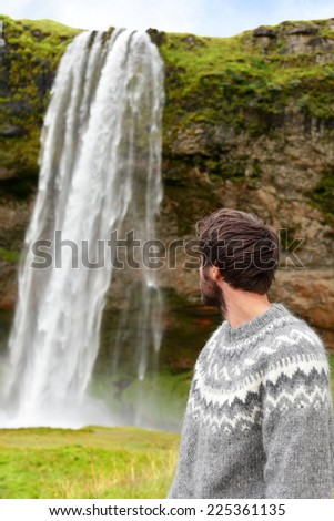 Icelandic sweater man by waterfall on Iceland outdoor smiling. Portrait of good looking male model  in nature landscape with tourist attraction Seljalandsfoss waterfall on Ring Road. - stock photo
