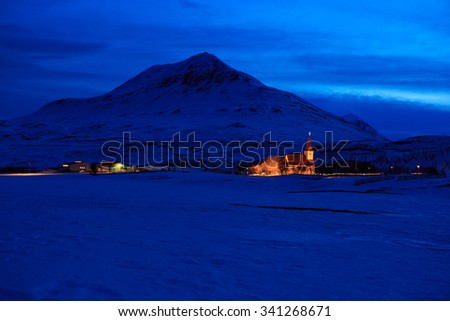 Icelandic winter landscape with church on the background of the mountains at dusk. near Akureyri, Iceland - stock photo