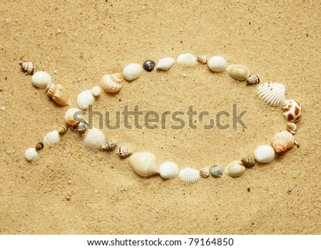 Ichthys, the Christian symbol of a fish, formed with small seashells on a smooth sandy beach - stock photo