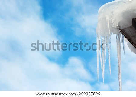 Icicles against a beautiful sky with clouds. - stock photo