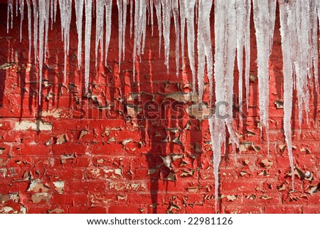 icicles against red wall - stock photo