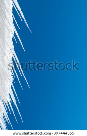 Icicles contrasted against a solid blue sky background. - stock photo