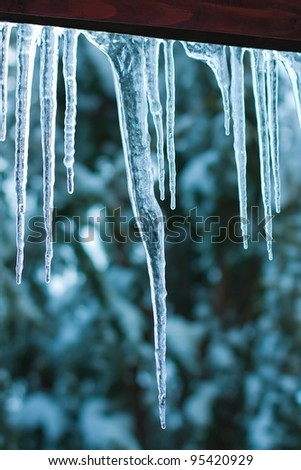 Icicles formed on a wooden roof. - stock photo