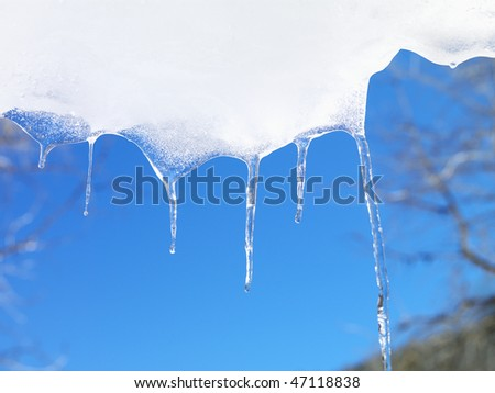 Icicles hanging down from snow and ice with a blue sky in the background. Horizontal shot. - stock photo