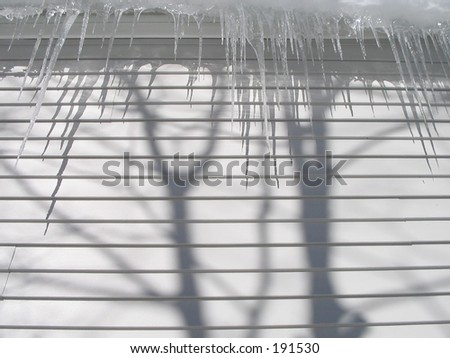 Icicles hanging from roof of a house with shadow from trees - stock photo