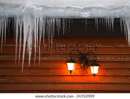 Icicles hanging from roof on idyllic wood cabin - stock photo