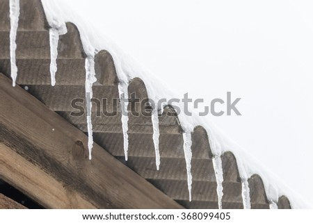 Icicles hanging from the roof - stock photo