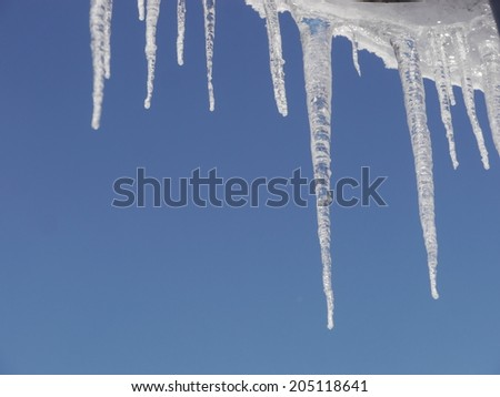 icicles hanging from the roof outside in landscape - stock photo