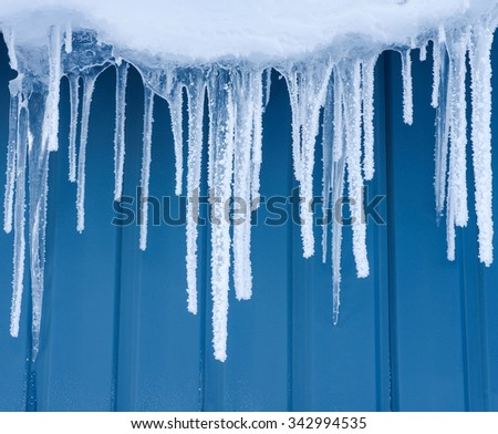 Icicles hanging from the wall covered with hoarfrost - stock photo