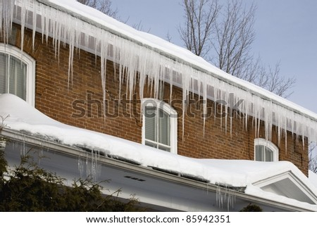 Icicles Hanging Off Rain Gutters - stock photo