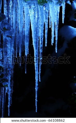 Icicles in cold blue light shining in the darkness at night - stock photo