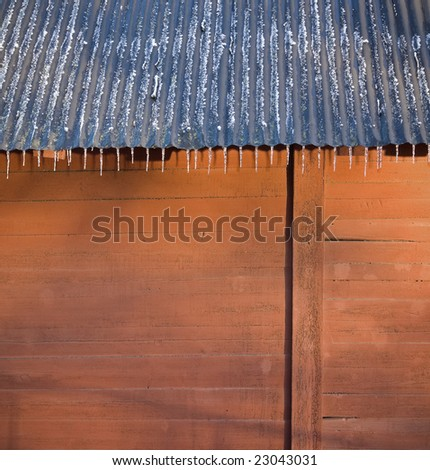Icicles on a red barn - stock photo