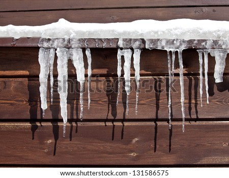 Icicles on Log Cabin - stock photo