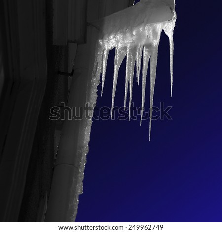 Icicles on pipe on facade of building at night, with dark blue sky - stock photo