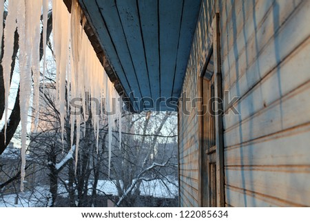 icicles on the roof of a wooden house with windows