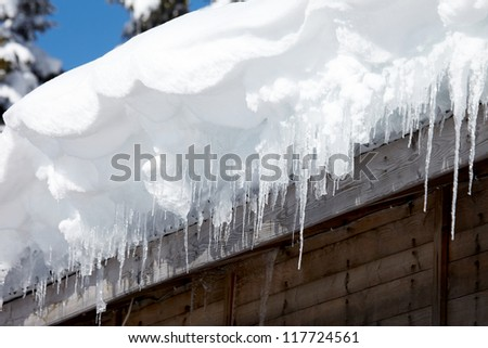 Icicles on the roof of the old house - stock photo