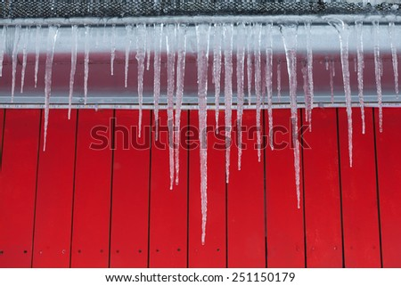 Icicles on the roof. Red wooden background.  - stock photo