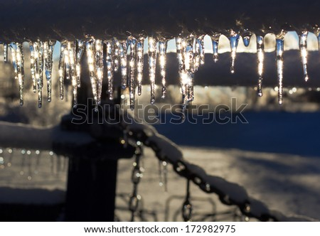 Icicles shining in the sun after an ice storm. - stock photo