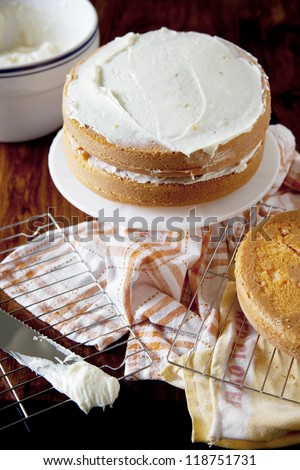 Icing a Layered Orange Cake - stock photo