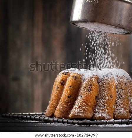 icing sugar falling on a freshly baked sweet cake, dark background - stock photo