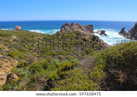Iconic ancient  Sugar Loaf Rock South Western Australia in the blue Indian Ocean is a popular fishing and hiking destination with its treeless green  dunes and  splashing waves on old eroded rocks.