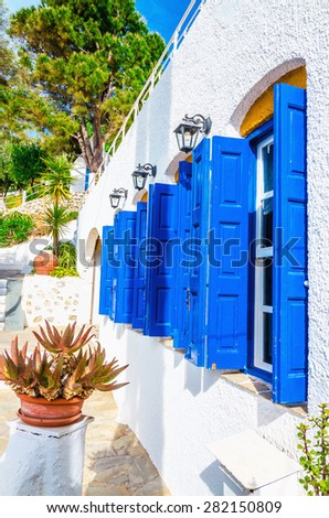 Iconic blue wooden shutters and white walls typical for Greece - stock photo