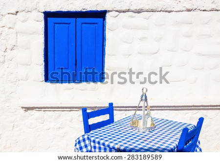 Iconic Greek restaurant with blue tablecloth and wooden chairs in front of stone white wall, Greece - stock photo